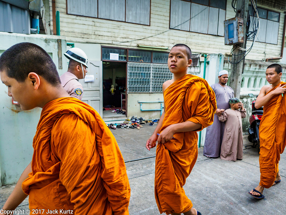 25 JUNE 2017 - BANGKOK, THAILAND: Buddhist monks walk past Ton Son Mosque during Eid al-Fitr services in the mosque. Eid al-Fitr is also called Feast of Breaking the Fast, the Sugar Feast, Bayram (Bajram), the Sweet Festival or Hari Raya Puasa and the Lesser Eid. It is an important Muslim religious holiday that marks the end of Ramadan, the Islamic holy month of fasting. Muslims are not allowed to fast on Eid. The holiday celebrates the conclusion of the 29 or 30 days of dawn-to-sunset fasting Muslims do during the month of Ramadan. Islam is the second largest religion in Thailand. Government sources say about 5% of Thais are Muslim, many in the Muslim community say the number is closer to 10%.    PHOTO BY JACK KURTZ