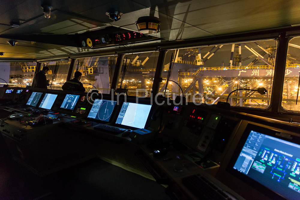 Crew members operate on the bridge of CMA CGM SAs Benjamin Franklin container ship as it pulls out of Guangzhou Nansha Container Port in Guangzhou, China, on Monday, Feb. 1, 2016. The Benjamin Franklin is the largest container ship ever to have docked at a U.S. port.