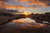 A lone person takes in the sunset view along the rocky coast of Maine, Acadia National Park, Maine, USA
