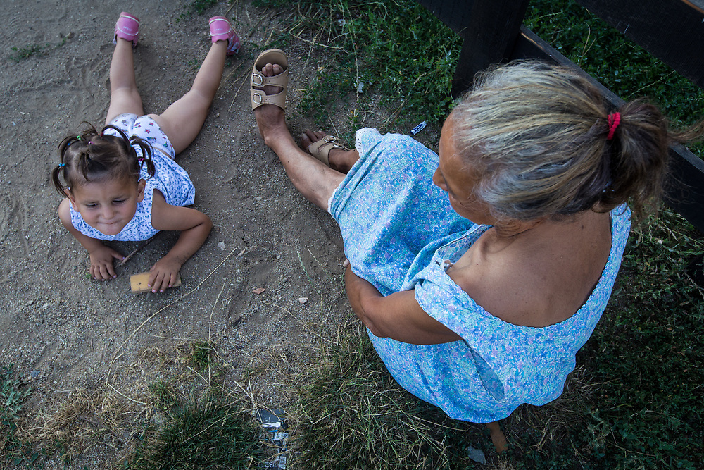 A Roma woman plays with her grandaughter near temporary housing built on top of a hill near the Pata Rat garbage dump.  In 2010, 260 Roma were expelled from their municipal housing in Cluj-Napoca's central Costei street and relocated here.                                                              © Daniel Barreto Mezzano