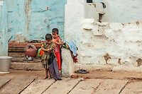 A child helps another with her dress in Hampi, India