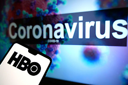 The HBO logo seen displayed on a mobile phone with an illustrative model of the Coronavirus displayed on a monitor in the background. Photo credit should read: James Warwick/EMPICS Entertainment
