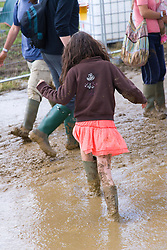 Young, festival goer forced to wear Wellington boots when heavy rain brings muddy ground at WOMAD (World of Music; Arts and Dance) Festival; Charlton Park; Malmesbury; 2007,