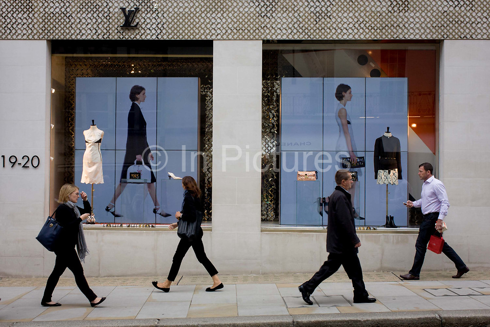 A walking theme shop window display at Louis Vuitton on Bond Street, central London. As passers-by make their way along the street in central London, they are alongside two video screens showing a loop of models on the catwalk, each also seen walking in profile, the same as the shoppers and workers. The location is 19-20 Bond Street, a street in the West End of London, connecting Piccadilly in the south to Oxford Street in the north. The street, consisting of two sections, has been a popular shopping area since the 18th century and is the home of many fashion outlets that sell prestigious and expensive items.