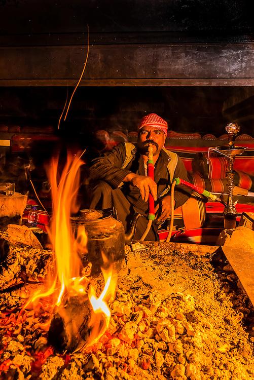 Bedouin man smoking sheesha (water pipe), Captain's Desert Camp, Arabian Desert, Wadi Rum, Jordan.