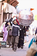 Workers in Marrakech carry their goods through the streets. Morocco travel photography