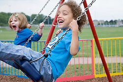 Little children playing on swings,