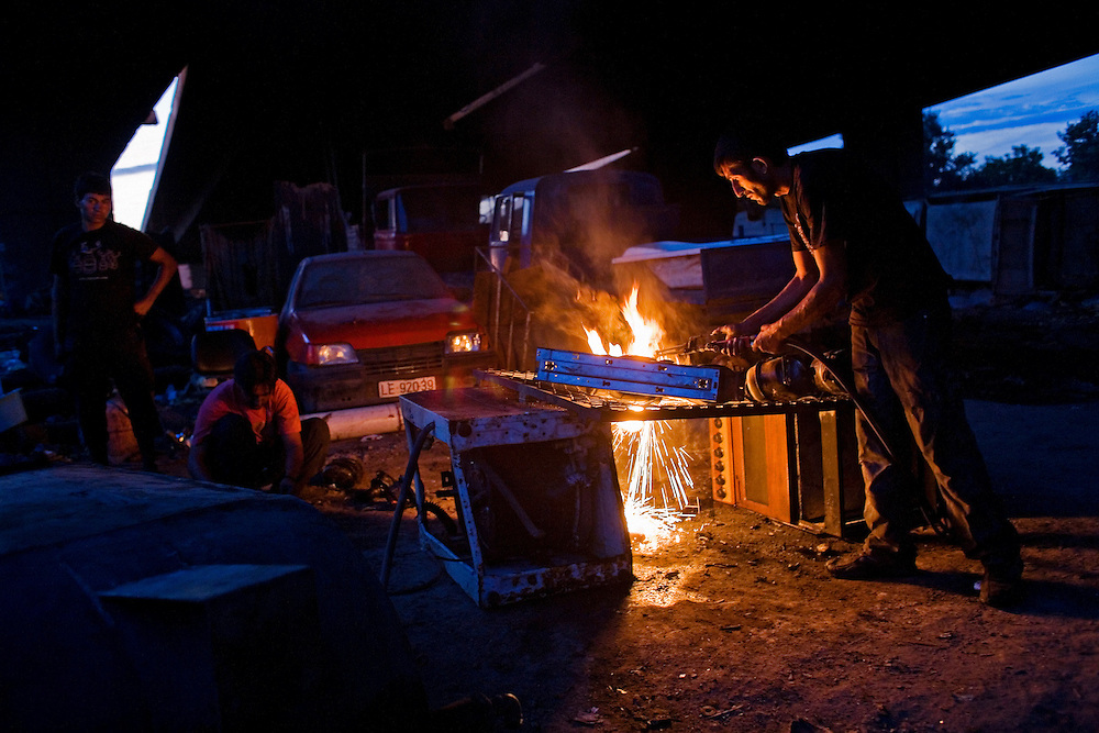 A man works at his metal salvage business in the Nova Gazela camp while children watch.