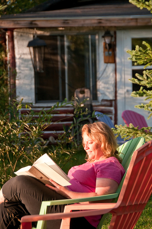 A woman relaxes and reads at the Republic Island Cottage near Republic Michigan.