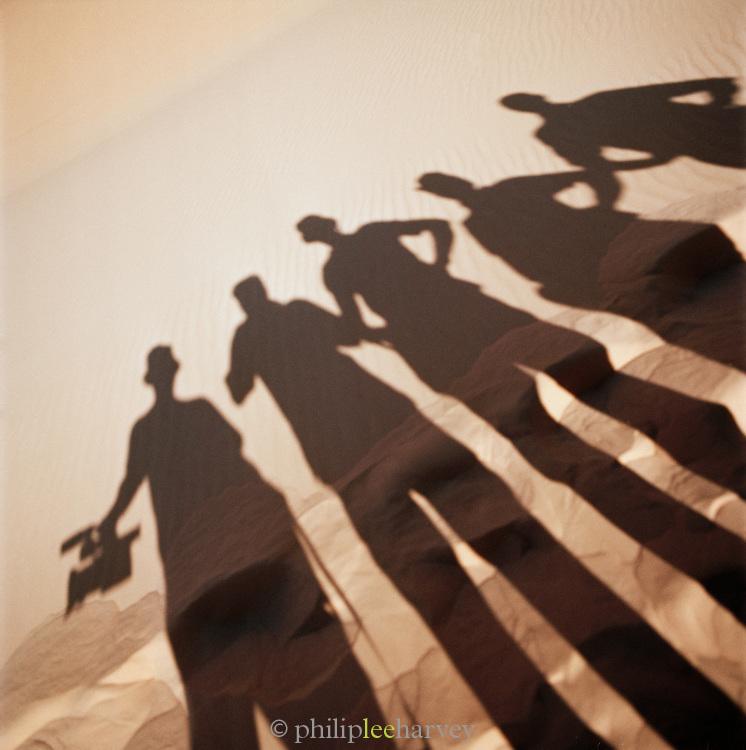 Shadows on the sand of 5 men and a video Camera, Sahara Desert, Libya