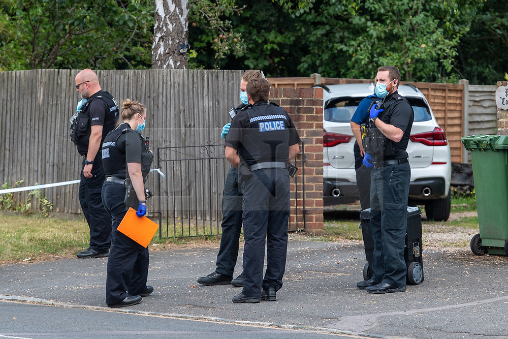 © Licensed to London News Pictures. 27/07/2021. Stoke Poges, UK. Police officers prepare to enter a property to gather evidence on Bells Hill in Stoke Poges, Buckinghamshire, following an assault on Monday 26 July at approximately 21:30BST. A man in his twenties suffered a serious leg injury following the assault which is understood to have involved a machete. Two men, aged 19 and 21, and a 20-year-old woman have been arrested on suspicion of section 18 wounding with intent. Photo credit: Peter Manning/LNP