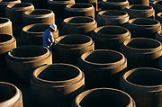 "Precast concrete pipes are prepared for distribution by a Mexican-born employee at Hanson Pipe & Products, Grand Prairie, Texas, USA. He cleans and inspects the tongue and groove seals of the upturned pipes wearing an obligatory hard hat and blue overalls. Precast concrete is made from a reusable mold or ""form"" and cured in a controlled environment, then transported to the construction site and lifted into place. Used in the construction of commercial building components, bridges, manholes and retaining walls, these products are the strongest pipe available, designed and plant tested to resist any load required with a design life of 70-100 years."
