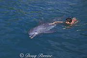 boy swims with captive bottlenose dolphin, Tursiops truncatus, in swim with dolphins program at Theater of the Sea, Islamorada, Florida, USA