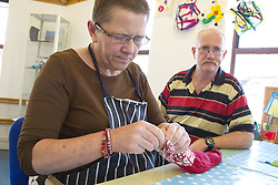 Felt making class for people with a visual impairment - untying felt from a roll.