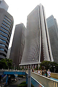 The 200-metre high Sompo Japan Head Office in Shinjuku's skyscraper district, with pedestrians crossing a bridge and two pigeons keeping watch. The building was completed in 1976 and designer by Uchida Shozo...