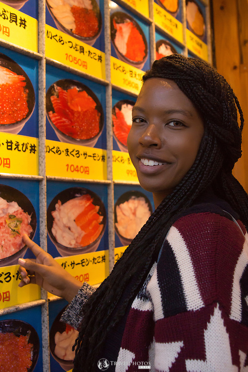 A young lady travelling in Japan looking at a seafood menu out side of a restaurant.
