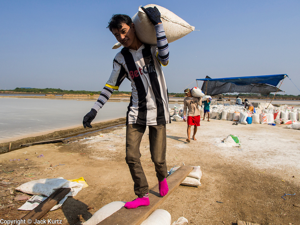 """28 MARCH 2014 - NA KHOK, SAMUT SAKHON, THAILAND:  Burmese migrant laborers load a truck with bags of salt on a Thai salt farm in Samut Sakhon province. Thai salt farmers south of Bangkok are experiencing a better than usual year this year because of the drought gripping Thailand. Some salt farmers say they could get an extra month of salt collection out of their fields because it has rained so little through the current dry season. Salt is normally collected from late February through May. Fields are flooded with sea water and salt is collected as the water evaporates. Last year, the salt season was shortened by more than a month because of unseasonable rains. The Thai government has warned farmers and consumers that 2014 may be a record dry year because an expected """"El Nino"""" weather pattern will block rain in mainland Southeast Asia. Salt has traditionally been harvested in tidal basins along the coast southwest of Bangkok but industrial development in the area has reduced the amount of land available for commercial salt production and now salt is mainly harvested in a small parts of Samut Songkhram and Samut Sakhon provinces.   PHOTO BY JACK KURTZ"""
