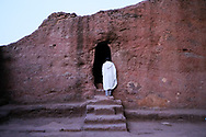 Pilgrim praying in front of one of the entrances to the Bet Maryam church complex of Lalibela, Ethiopia