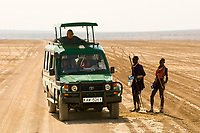 Tourists in a safari vehicle stop to talk with Maasai warriors, Amboseli National Park, Kenya