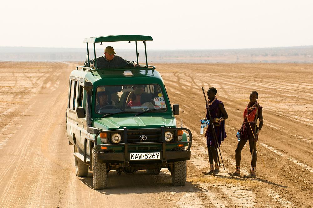 Tourists in a safari vehicle stop to talk with Maasai warriors, Amboseli National Park, Kenya