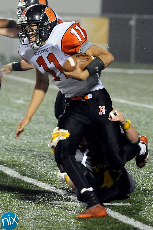 Trojans quarterback Damian Bertino (11) is sacked by a Vikings defender during the Northwest Cabarrus Trojans at Central Cabarrus Vikings high school football game on Friday night.