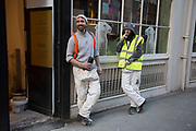 Two workers standing outside taking a break while two Llamas peer from the window behind them in London, England, United Kingdom.