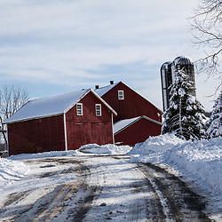 A red barn, silo, and trees after road has been plowed.