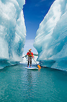 A woman on stand up paddle board (SUP) explores an iceberg canyon on Bear Lake in Kenai Fjords National Park, Alaska.