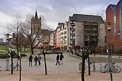 "Cologne, Germany, Jan. 2012 - Pedestrians walk along the Rhein river promenade in the ""Old Town"" district, in Cologne, Germany. The spire of Great St. Martin's church is seen in the background. (Photo © Jock Fistick)."