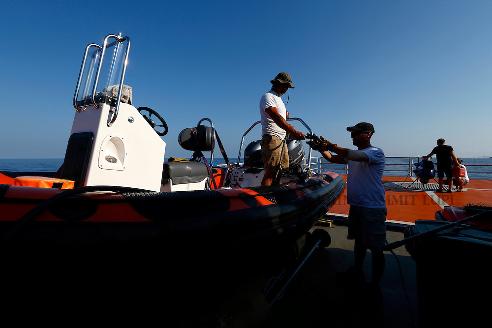 Crew members of the Migrant Offshore Aid Station (MOAS) ship MV Phoenix prepare a RHIB (rigid hulled inflatable boat) and a Schiebel Camcopter S-100 drone for a migrant search operation off the coast of Libya August 7, 2015.  REUTERS/Darrin Zammit Lupi <br /> MALTA OUT. NO COMMERCIAL OR EDITORIAL SALES IN MALTA