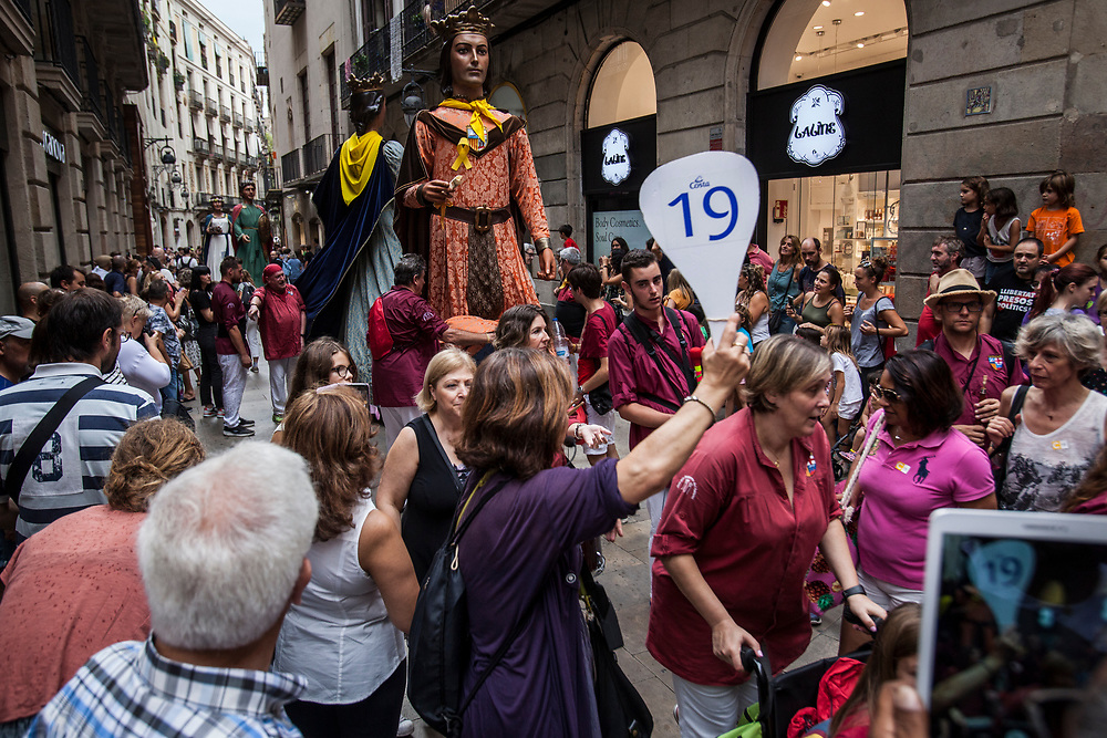 A group of cruise passengers trying to make their way through a parade in the Gothic Quarter. As a consequence of tourist pressure, the population of central neighbourhoods is decreasing and neighbourhood activities are on the decline, leading to a gradual process of cultural identity loss.