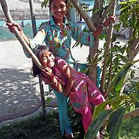 Asia, Nepal, Kathmandu. Two sisters enjoy garden tree.
