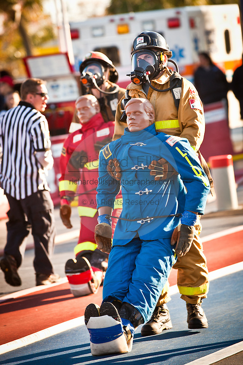 Racing neck and neck two firefighters drags a 175-pound mannequin backwards wearing full firefighting gear and working against the clock during the international finals of the Firefighter Combat Challenge on November 18, 2011 in Myrtle Beach, South Carolina.