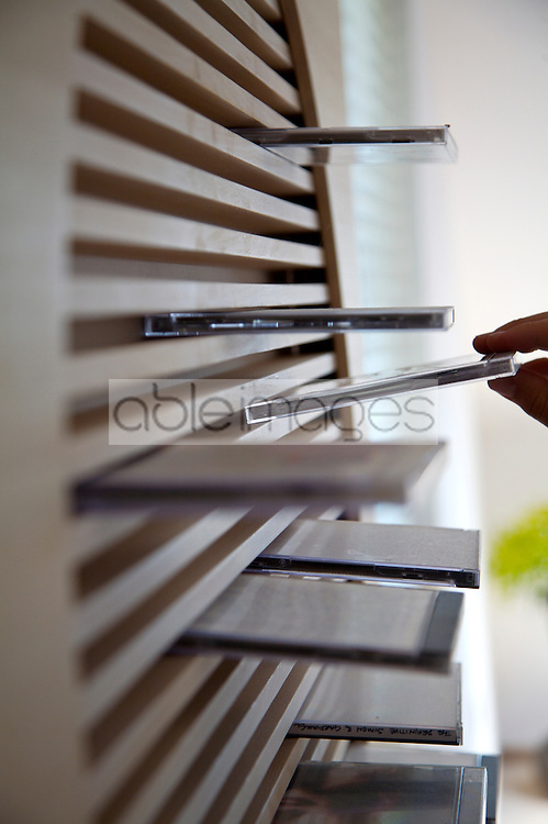 Man's hand choosing CD-ROM from compact disc storage unit