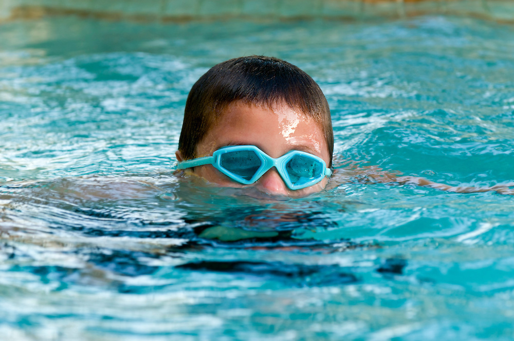 Child wearing googles and submerging in a swimming pool.