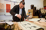 Skilled Chinese calligrapher at work in gift shop of the Jade Buddha Temple, Shanghai, China