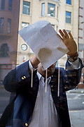 A obscured businessman leans his A4 paper on a cafe window to write some notes, on 5th October, 2017, in the City of London, England.