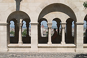 The Hungarian Parliament Building built in a gothic revival style from 1896-1904 seen through the arches of the Halászbástya or Fisherman's Bastion, Buda Castle. Budapest, Hungary, 2005