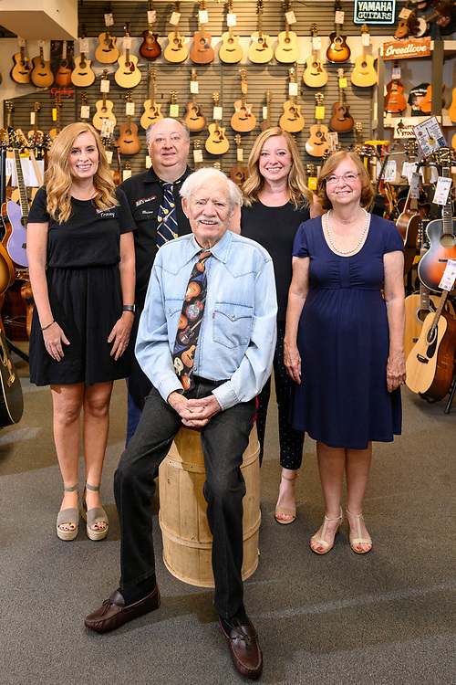 Catonsville, Maryland - August 10, 2021: Bill's Music founder Bill Higgins stands with his wife Nancy and their kids Jamie Reese, Tracey Kern, and Brian Higgins at the family store Tuesday August 10, 2021. Bill officially retired in 2020 out of concern for his health and COVID-19, but he finds it hard to stay away from the store that has his face on it. His children have taken over day-to-day operations of the 56-year-old business.<br /> <br /> CREDIT: Matt Roth for Baltimore Magazine
