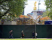 © Licensed to London News Pictures. 06/06/2012. London, UK. A family look through a security wall into the construction site in front of Buckingham Palace. Workmen begin the task of deconstructing the stages and scaffolding platforms put in place for the celebrations.  The Royal Jubilee celebrations. Great Britain is celebrating the 60th  anniversary of the countries Monarch HRH Queen Elizabeth II accession to the throne this weekend Photo credit : Stephen Simpson/LNP