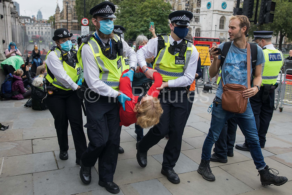 Metropolitan Police officers arrest a climate activist from Extinction Rebellion who had occupied the pavement outside the Houses of Parliament on 3 September 2020 in London, United Kingdom. Extinction Rebellion activists are attending a series of September Rebellion protests around the UK to call on politicians to back the Climate and Ecological Emergency Bill CEE Bill which requires, among other measures, a serious plan to deal with the UK's share of emissions and to halt critical rises in global temperatures and for ordinary people to be involved in future environmental planning by means of a Citizens' Assembly.