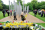 People lay flowers at the memorial to the victims of the July 7th London bombings, at Hyde Park in London. Thursday marks the sixth anniversary of the July 7 bombings, which killed 52 people and injured more than 770 in terrorist attacks.