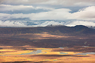 Fresh snow on the Alaska Range signals the coming of winter overlooking the Maclaren River Valley in Alaska. Autumn. Morning.