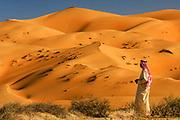 "An Emirati driver returns to his vehicle in the ""Empty Quarter""of Abu Dhabi Emirate, near the Saudi Arabian border."