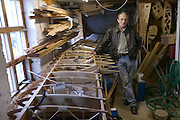 Bjorn Thoroddson, father of the Thoroddson family, originally photographed in 1993 for the book Material World.  Bjorn is seen here in his home garage workshop with parts of an airplane wing he is building. Hafnarfjordur, near Reykjavik, Iceland, 2004. MODEL RELEASED.