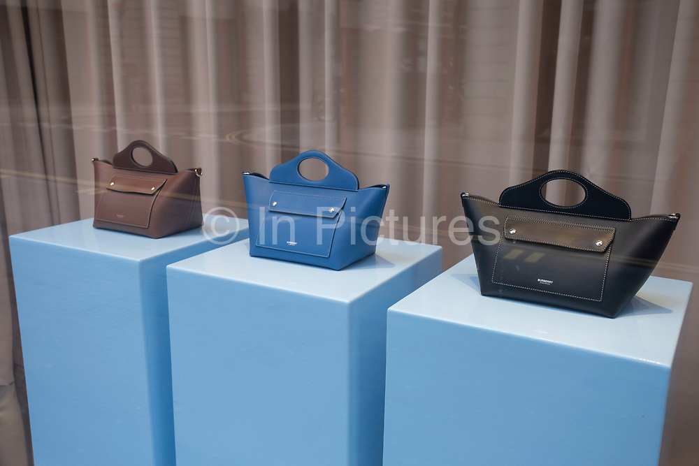 Burberry handbags in their shop window on 5th March 2021 in London, England, United Kingdom. Burberry is a British luxury fashion house headquartered in London, England. It currently designs and distributes ready to wear clothes, and leather goods etc.