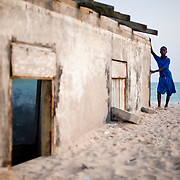 Torgborfio Obodai, a schoolboy from Totope, a fishing village near Ada, Ghana, stands by a house that is being claimed by the sea on 7 March 2010.