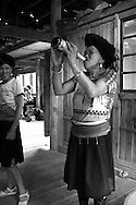 Ethnic woman drinks beer holding the bottle with her two hands. Area of Ping'An, Guangxi, China, Asia