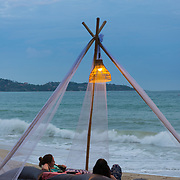 Girls relaxing on inflatable beach beds at dusk in Ssmui Lamai beach, Thailand