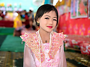 Portrait of a girl preparing for a Shinbyu Novice Ceremony on 21st March 2016 in Mo Bye village, Shan State, Myanmar. In Myanmar, it is customary for boys to enter the monastery as a Buddhist novice between the age of ten and 20 years old although they can be as young as four, for at least one week. Whilst the novice-to-be is the centre of attention, his sister may at the same time have an ear-piercing ceremony or na htwin using a gold needle, and dress as a royal princess herself